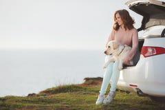 Fille sur la plage avec un Labrador blanc et une voiture blanche Images stock