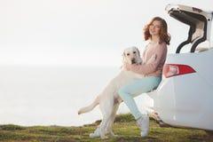 Fille sur la plage avec un Labrador blanc et une voiture blanche Photo stock