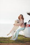 Fille sur la plage avec un Labrador blanc et une voiture blanche Images libres de droits