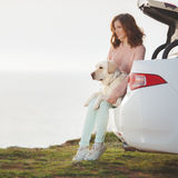Fille sur la plage avec un Labrador blanc et une voiture blanche Photos stock