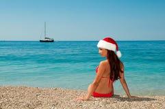 Fille sur la plage dans un chapeau de Noël. Photographie stock