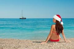 Fille sur la plage dans un chapeau de Noël. Image stock