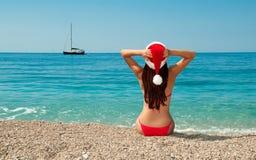 Fille sur la plage dans un chapeau de Noël. Photo libre de droits