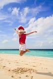 Fille sur la plage en rouge de Santa Image stock