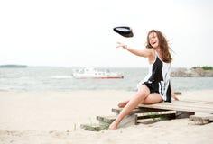 Fille sur la plage projetant son capuchon et rires Images libres de droits