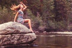 Fille sur la roche par le lac Photographie stock libre de droits