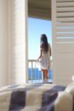 Fille sur le balcon regardant la mer Photos stock