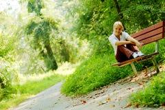 Fille sur le banc de forêt Photo libre de droits