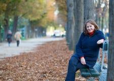 Fille sur le banc en parc un jour d'automne Photographie stock libre de droits
