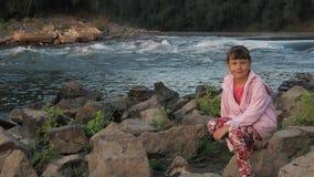 Fille sur le côté de fleuve Une petite fille dans une veste rose sur la banque d'une rivière rapide clips vidéos
