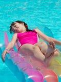 Fille sur le lilo dans la piscine photo libre de droits