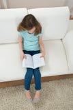 Fille sur le livre de relevé de sofa Photographie stock libre de droits