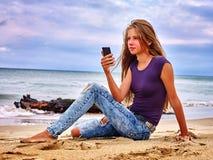 Fille sur le sable près de l'aide d'appel de mer par le téléphone Images stock