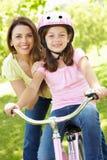 Fille sur le vélo avec la mère Photographie stock libre de droits