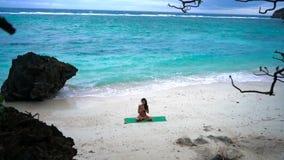 Fille sur le yoga de pratique de plage banque de vidéos