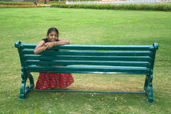 Fille sur un banc de jardin Images stock