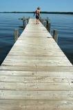 Fille sur un dock de bord de lac Photographie stock