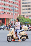 Fille sur un e-vélo au centre de la ville, Kunming, Chine Photo stock