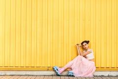 Fille sur un fond jaune de mur Photo stock