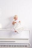 Fille sur un piano blanc Photographie stock libre de droits