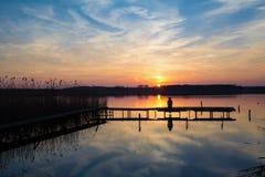 Fille sur un port à un lac sur le coucher du soleil Photographie stock libre de droits