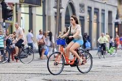 Fille sur un vélo de location près de place de barrage, Amsterdam, Pays-Bas Images libres de droits