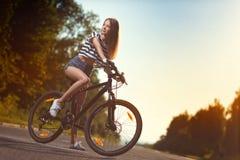 Fille sur une bicyclette au coucher du soleil Image stock