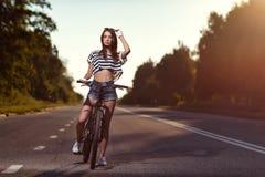 Fille sur une bicyclette au coucher du soleil Photos libres de droits