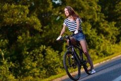Fille sur une bicyclette au coucher du soleil Photo stock