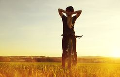 Fille sur une bicyclette dans le coucher du soleil Images stock