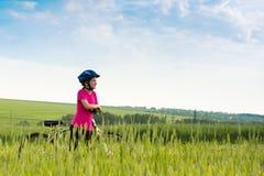Fille sur une bicyclette dans le paysage rural Photographie stock libre de droits