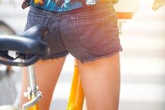 Fille sur une bicyclette de ville à un croisement de rue, Milan, Italie image libre de droits