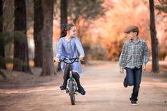 Fille sur une bicyclette et un garçon courant à coté sur le chemin d'un parc photos stock