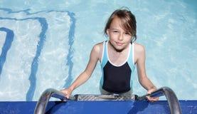 Fille sur une échelle entrant dans une piscine Photographie stock libre de droits
