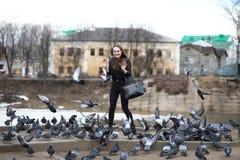 Fille sur une promenade en parc et un troupeau des pigeons image stock