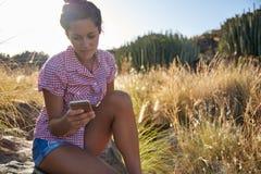 Fille sur une roche regardant le téléphone portable Photos stock