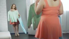 Fille surdimensionnée choisissant le chemisier dans le vestiaire à la boutique, plus la mode de taille banque de vidéos