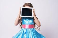 Fille tablette Enfant de portrait robe bleu technologies Photo stock