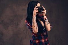 Fille tatouée prenant une photo regardant la caméra dans un studio images stock