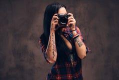 Fille tatouée prenant une photo regardant la caméra dans un studio image libre de droits