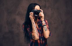 Fille tatouée prenant une photo regardant la caméra dans un studio photos stock
