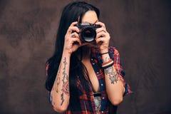 Fille tatouée prenant une photo regardant la caméra dans un studio photo libre de droits