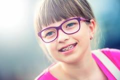 Fille teen Pré ado Fille avec des verres Fille avec des accolades de dents Accolades et verres de port de dents de jeune fille bl Images stock