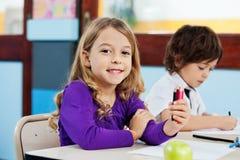 Fille tenant des crayons de couleur avec le dessin d'ami dedans Photographie stock libre de droits