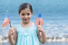 Fille tenant des drapeaux des Etats-Unis dans la plage Image stock