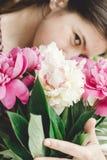 Fille tenant et sentant le beau bouquet de rose et blanc de pivoines à la vieille fenêtre en bois rustique D?cor floral et dispos photos libres de droits
