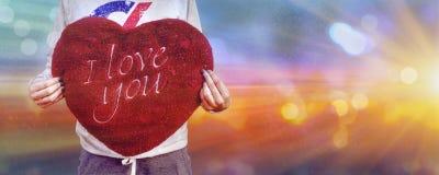 Fille tenant je t'aime l'oreiller de coeur, effet abstrait de bokeh de soleil image libre de droits