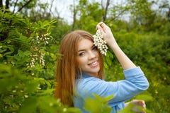 Fille tenant l'acacia de fleurs Image stock