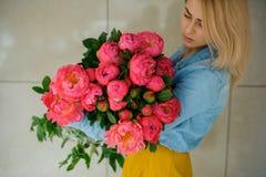 Fille tenant la fleur rose fraîche de pivoine Photo libre de droits