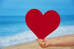 Fille tenant la forme de coeur sur la plage Image libre de droits